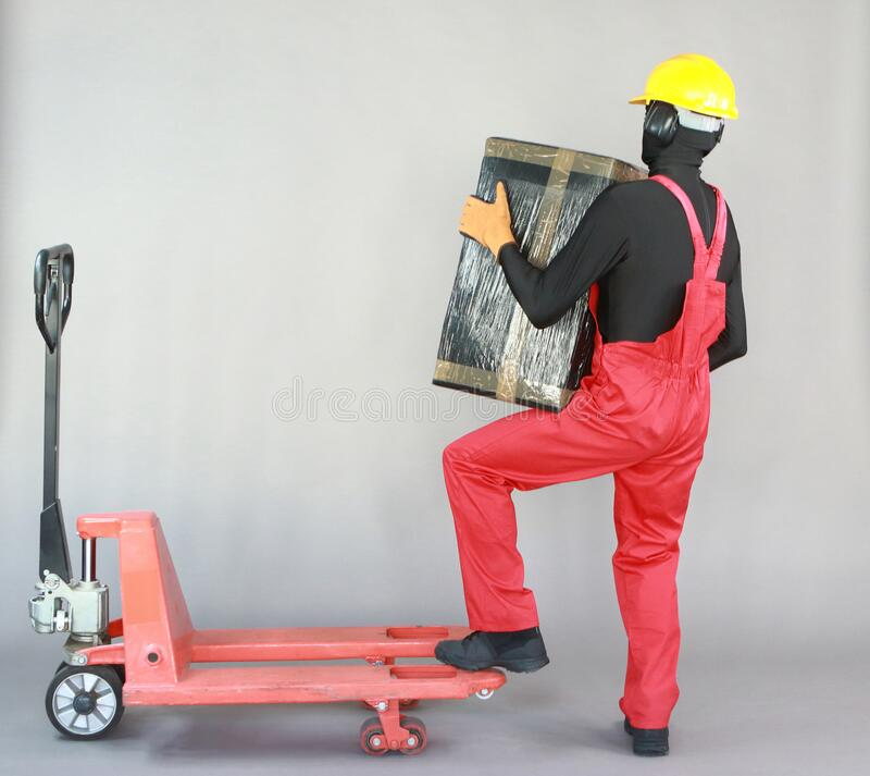 Anonymous worker lifting  heavy package. Profile view. royalty free stock images