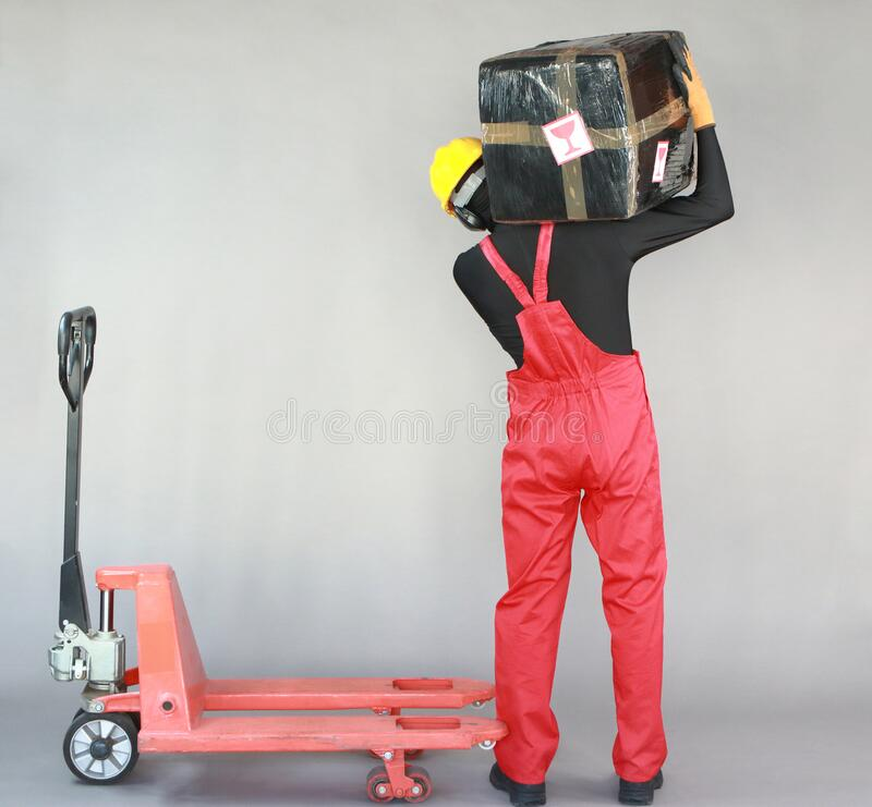 Anonymous worker lifting  heavy package. Back view. royalty free stock photo