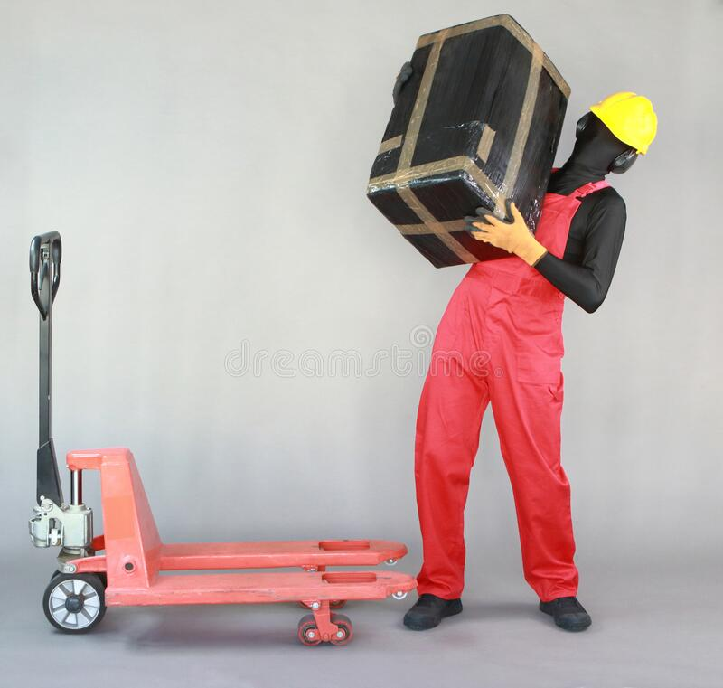 Anonymous worker lifting  heavy package. Front view. royalty free stock images