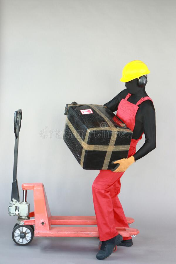 Anonymous worker lifting  heavy package. Profile view. royalty free stock photo
