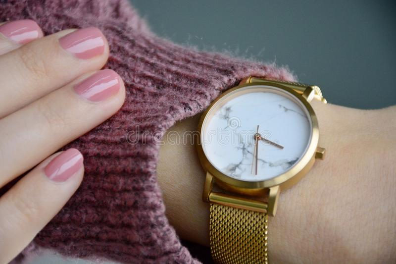 Young woman looking at her watch. Anonymous young woman looking at her rose gold watch. Woman`s hand with pink manicure. Watching the time royalty free stock photography