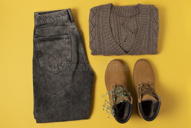 Anordnung der Herbstkleidung in warmen Farben auf gelbem Hintergrund flach gelegene Jeans, Jumper, Stiefel lizenzfreie stockfotografie