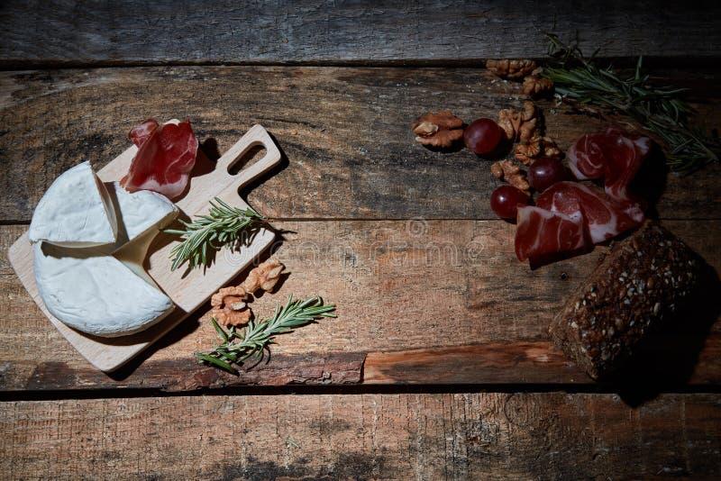 Anordnung für Feinschmecker sortierte Aperitifs des Käses und des Prosciutto auf Holzoberfläche mit Walnüssen und Brot stockfotos