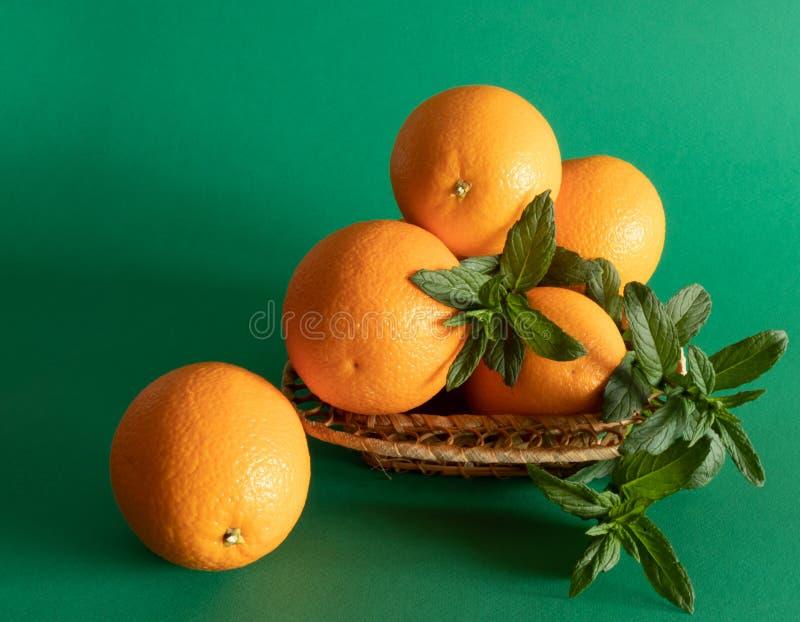 Anordnung f?r Orangen in einer Sch?ssel verziert mit Minze im nat?rlichen Licht stockbilder