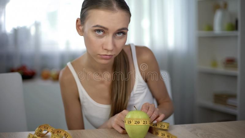 Anorexic girl measuring apple with tape, counting calories and body mass index stock images