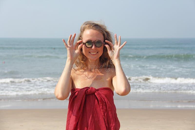 Anormal bonito da menina em um vestido vermelho e em um cabelo louro, no fundo do mar Menina do verão em vidros de madeira redond imagens de stock royalty free