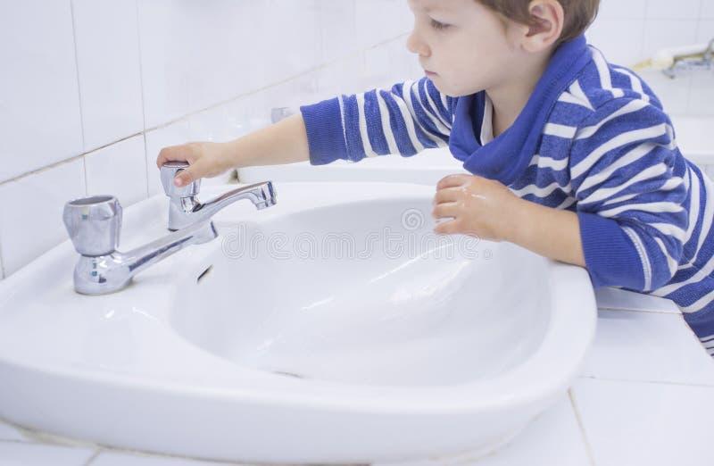 3 anos de mãos de lavagem do menino no dissipador adaptado da escola fotos de stock