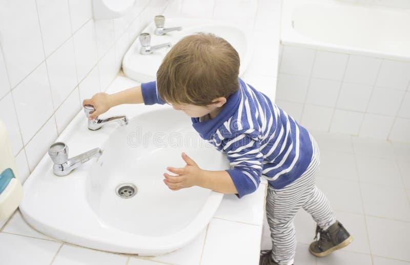 3 anos de mãos de lavagem do menino no dissipador adaptado da escola imagens de stock