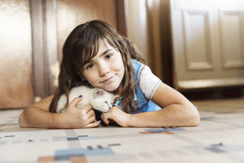 7 anos de menina idosa com gatinho em casa no assoalho da cozinha, imagens de stock