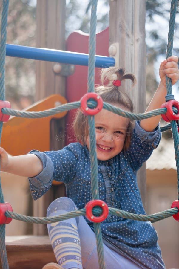 4 anos de menina que joga na área do campo de jogos fotografia de stock