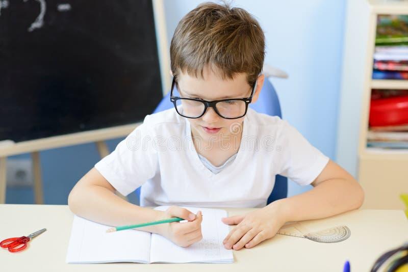 7 anos de menino idoso resolvem a tabela de multiplicação foto de stock