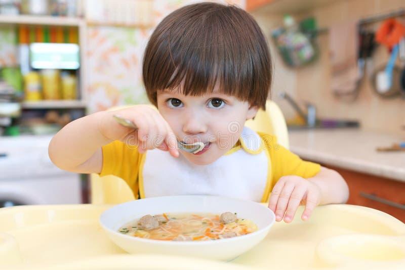 2 anos de menino que come a sopa com a cozinha das bolas de carne em casa imagens de stock