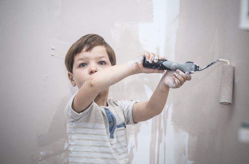 3 anos de rapaz pequeno bonito com rolo de pintura ? disposi??o fotos de stock royalty free
