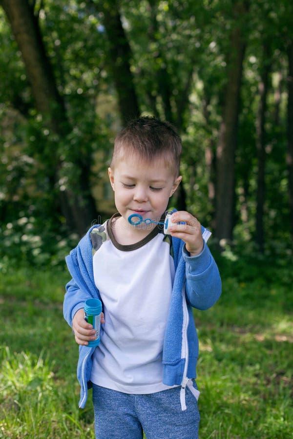 4 anos de rapaz pequeno com bolhas de sabão em árvores do verde do verão estacionam, tempo de lazer engraçado Menino nas bolhas d imagens de stock royalty free