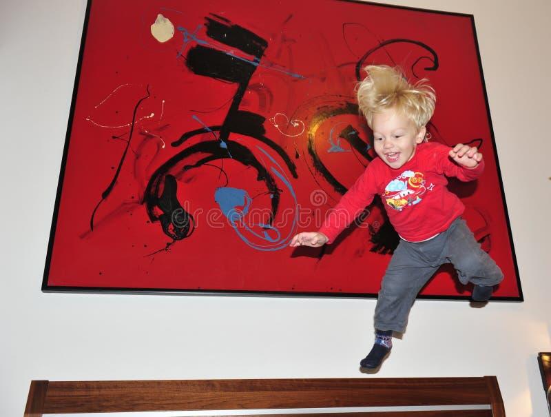 2 anos felizes da criança que salta na cama fotografia de stock royalty free