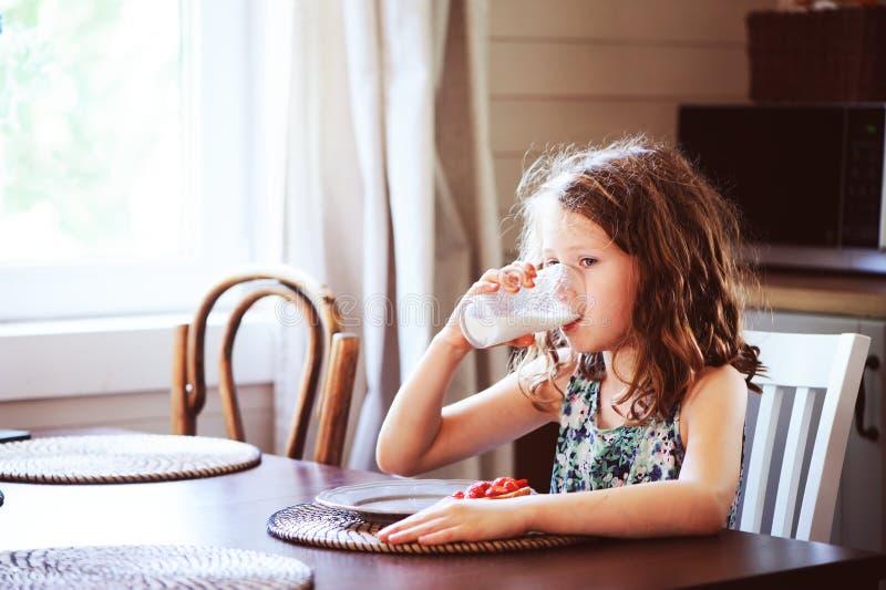 8 anos felizes da menina idosa da criança que come o café da manhã na cozinha do país imagem de stock royalty free