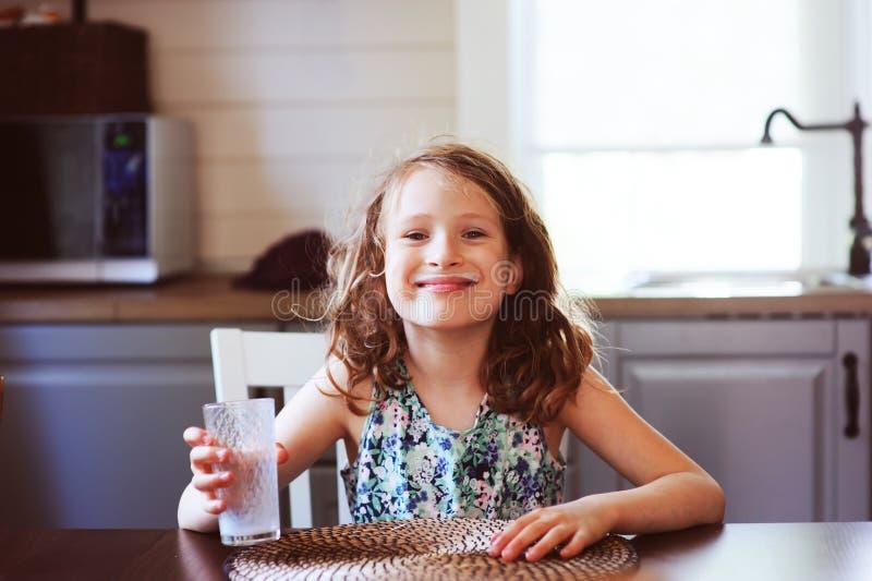 8 anos felizes da menina idosa da criança que come o café da manhã na cozinha do país, leite bebendo fotografia de stock