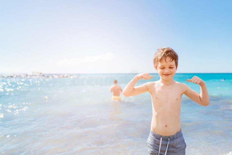 7 anos felizes do menino no gesto do sucesso da vitória na praia fotos de stock royalty free