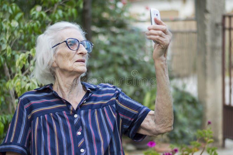 Anos noventas da avó idosa que toma um selfie com um smartphone no th fotos de stock