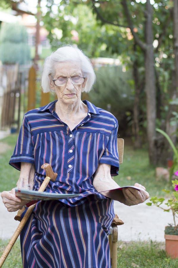 Anos noventas de senhora idosa que lê os jornais no quintal imagem de stock