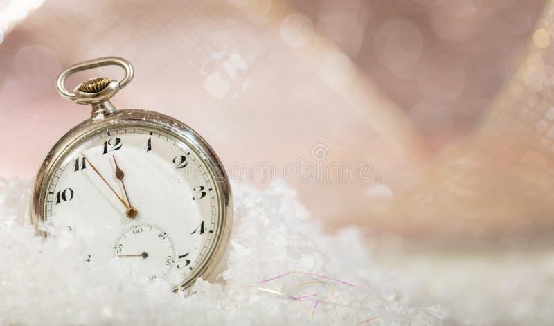 Anos novos da contagem regressiva da véspera Minutos à meia-noite em um relógio de bolso antiquado, fundo nevado do bokeh imagens de stock