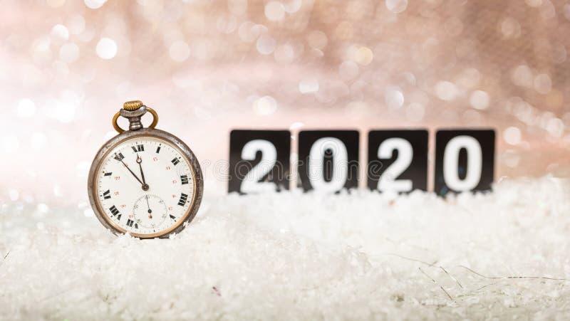 2020 anos novos de celebração da véspera Minutos à meia-noite em um relógio velho, bokeh festivo foto de stock