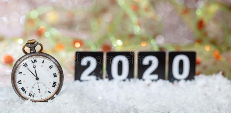 2020 anos novos de celebração da véspera Minutos à meia-noite em um relógio velho, fundo festivo do bokeh foto de stock