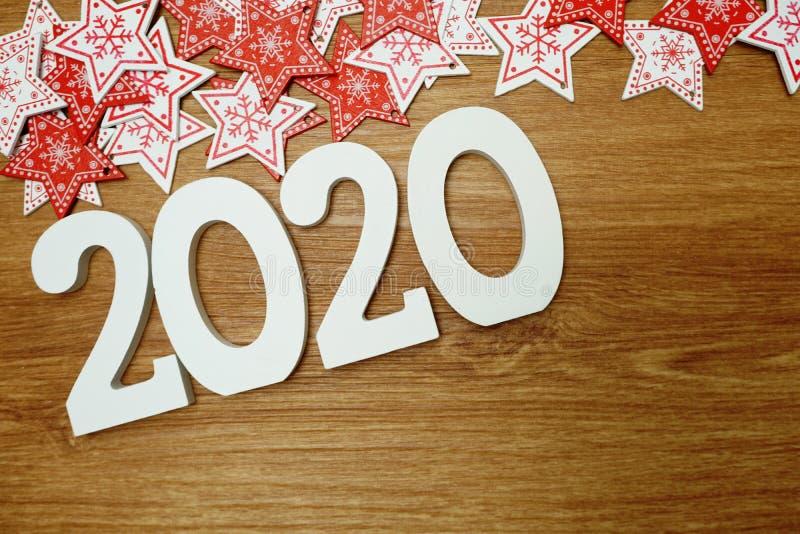 2020 anos novos felizes com a decora??o branca e vermelha do ornamento da estrela no fundo de madeira imagens de stock royalty free