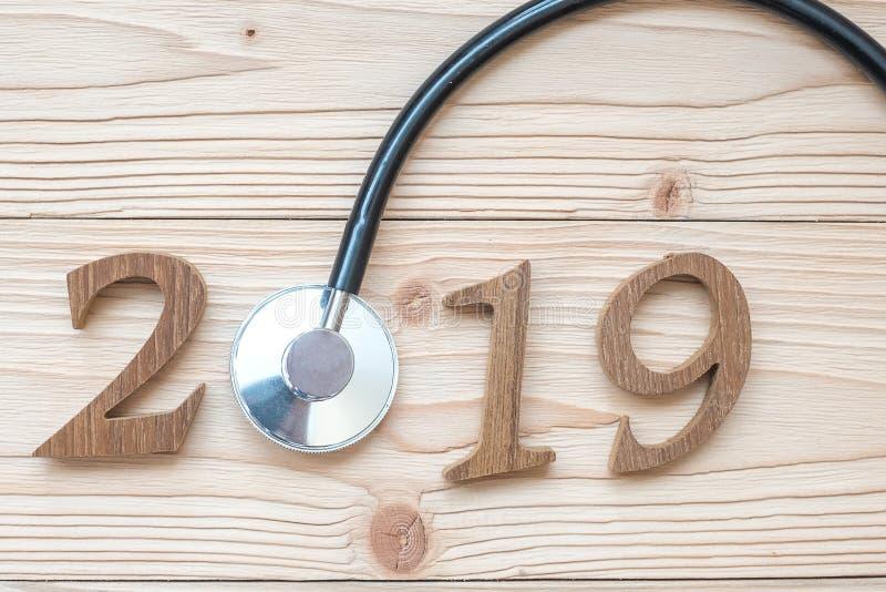 2019 anos novos felizes para cuidados médicos, bem-estar e o conceito médico Estetoscópio com número de madeira na tabela foto de stock