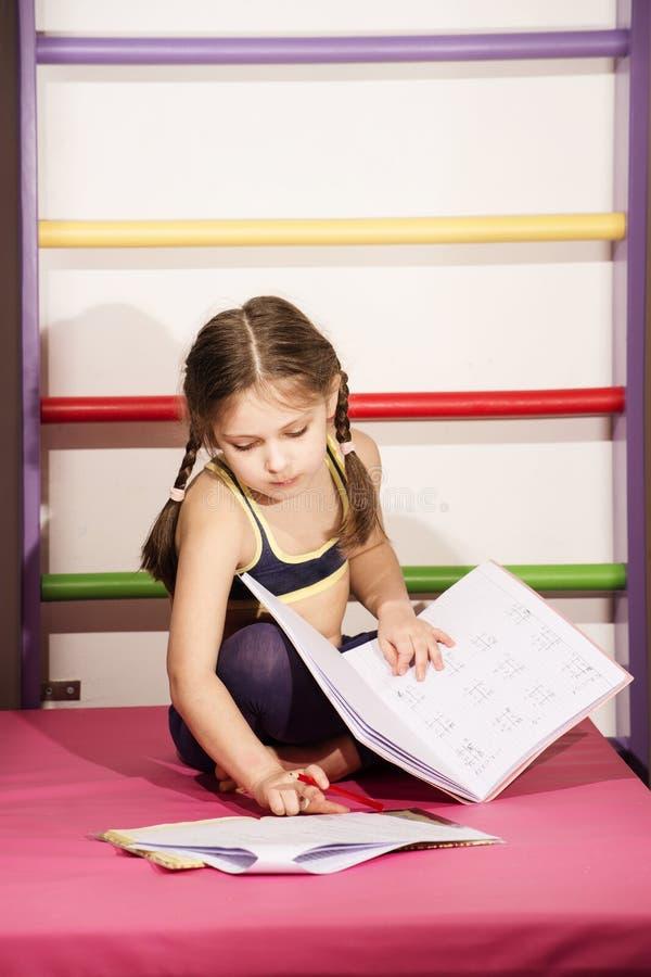 6-8 anos pouco caucasianos da menina idosa que faz um lições do ` s no gym foto de stock royalty free