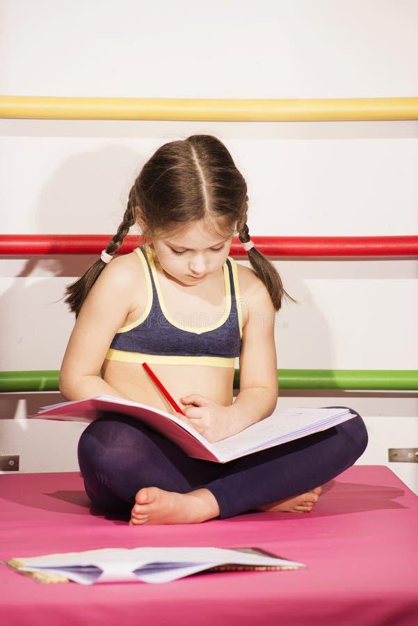 6-8 anos pouco caucasianos da menina idosa que faz um lições do ` s no gym fotografia de stock royalty free