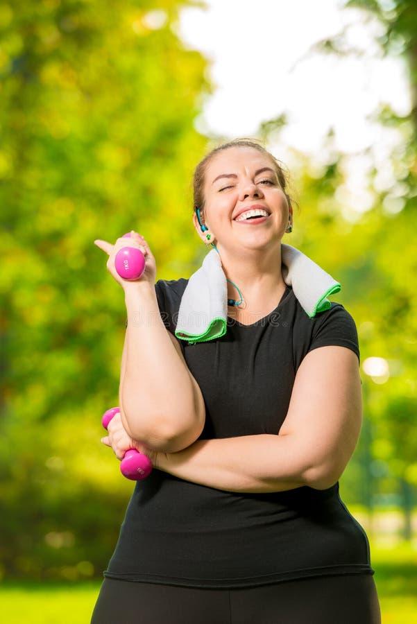 30 anos velho mais a mulher do tamanho que faz pesos durante um parque do verão fotografia de stock royalty free