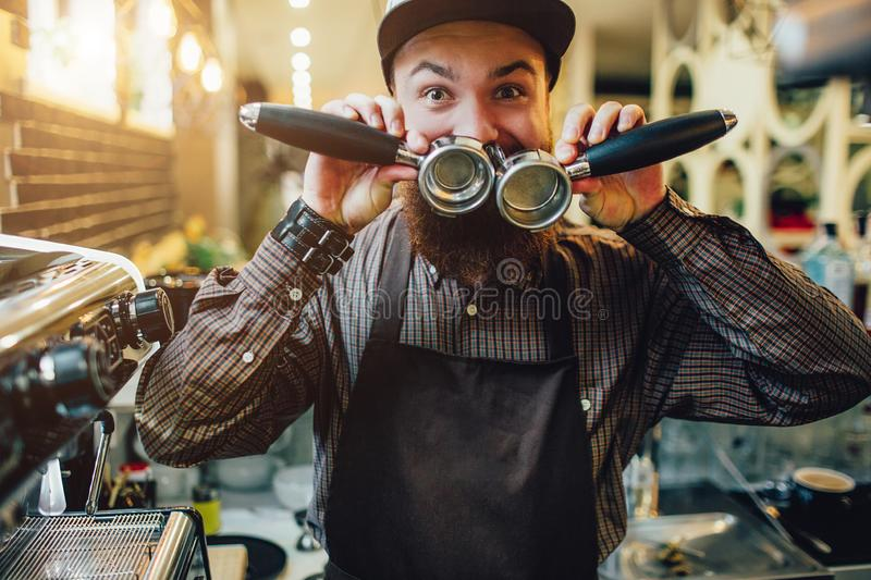 Another picture of happy and funny young barista holding to cezve and cover mouth with them. He looks on camera. Guy stock images