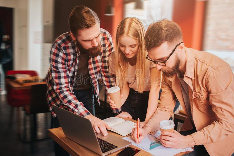 Another picture of three business partners working on project. They have the meeting in cafe. Guys and girl studying stock image