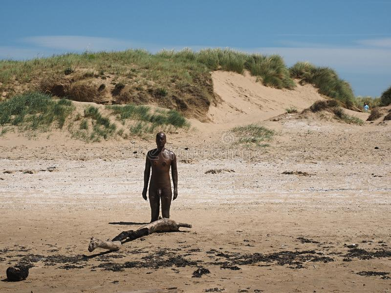Another Place is a series of 100 cast-iron life-size figures by Antony Gormley standing on Crosby beach looking out to sea. Liverpool royalty free stock image