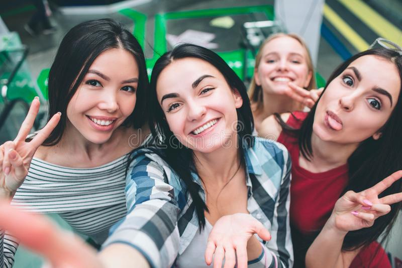 Another selfie of attractive young women having a lot of fun together. Girl in red dress is showing her tongue while. Another girls are just posing stock images