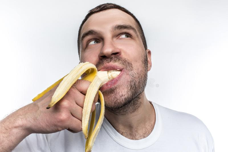 Another strange picture of unshaved guy eating ripe banana. He is biting a big piece of fruit. Man is enjoying the. Mmoment and looking somewhere aside stock photos