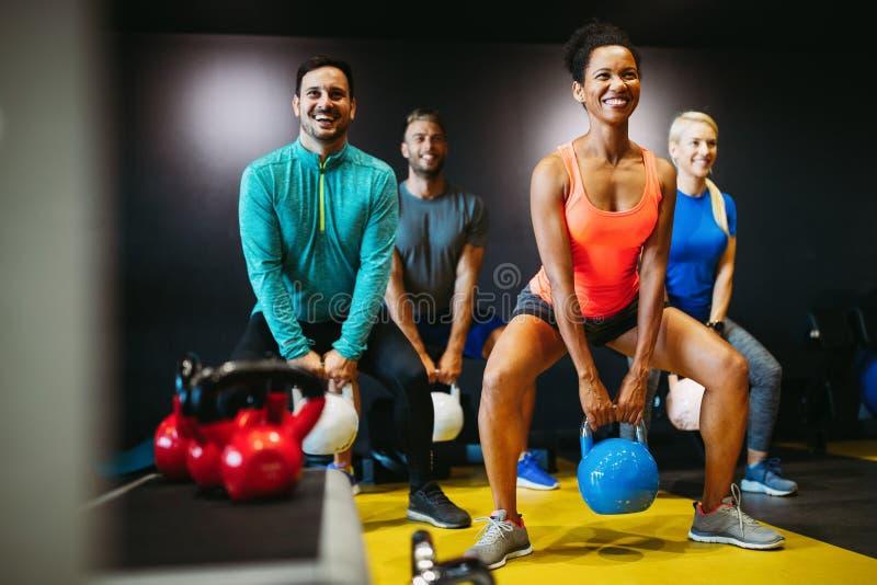 Anpassa människor som arbetar i träningsklass på gymmet royaltyfri bild