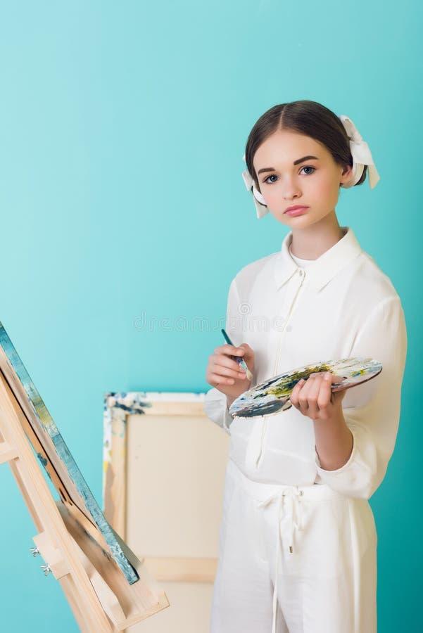 Anreden der jugendlich Künstlermalerei auf Gestell mit Bürste und Palette lizenzfreies stockbild