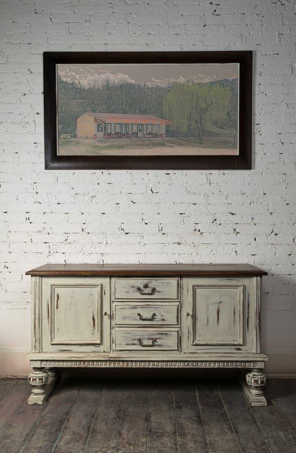 Anrichte und gehangenes Malen über Bretterboden und Ziegelsteinwand lizenzfreies stockfoto