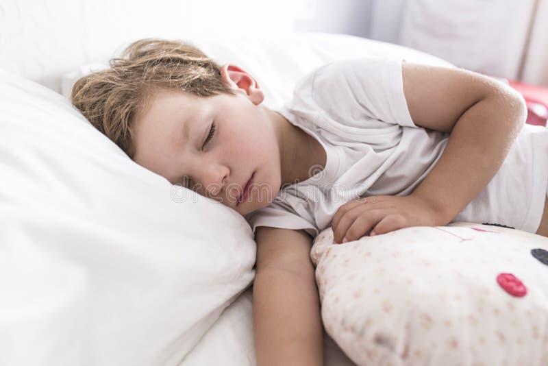 3 ans de garçon d'enfant en bas âge dormant la sièste sur le lit photo libre de droits