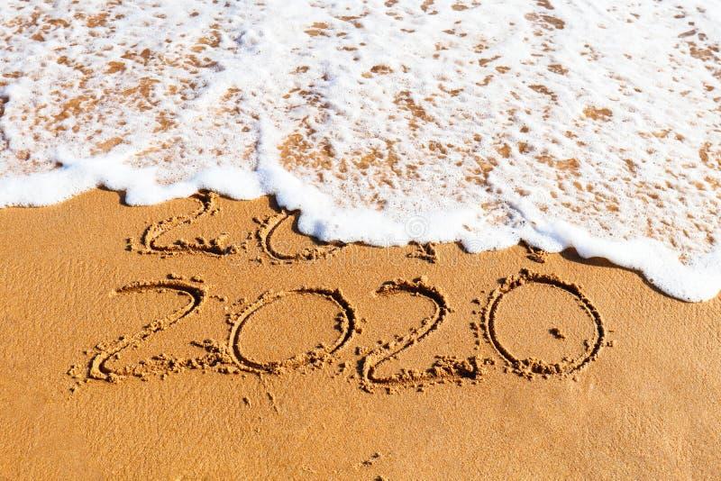 2020 ans dessinés sur le sable enlevé par une vague image stock