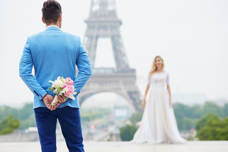 Ansa att dölja bröllopbuketten bak hans baksida arkivbilder