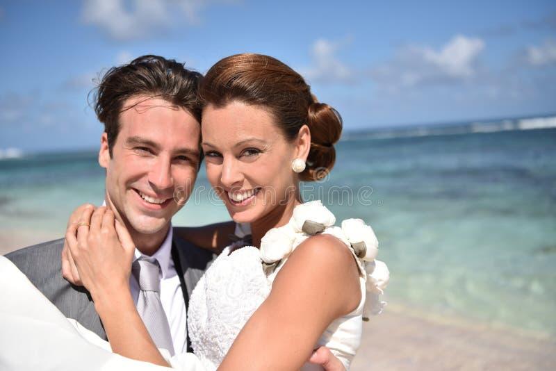 Ansa den hållande bruden i hans armar på stranden arkivfoton