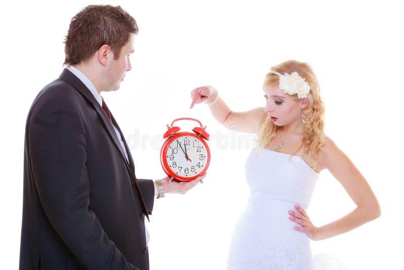 Ansa hållande stort rött den klockaskrika och bruden royaltyfria bilder