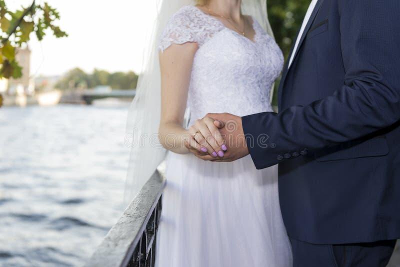 Ansa i en blå dräkt som rymmer handen av en brud i vita dres royaltyfri foto