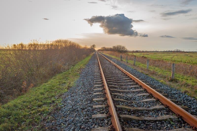 Anscheinend endlose lange einzelne Schienenstränge bei Sonnenuntergang stockbilder