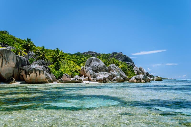 Anse źródła d «Argent - Sławni granitowi głazy na raj tropikalnej plaży z płytką turkus wodą Los Angeles Digue zdjęcia royalty free