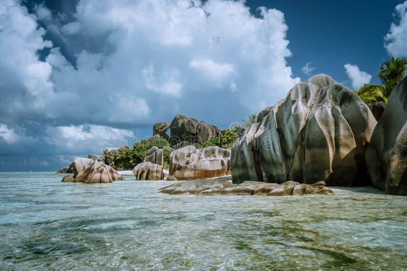 Anse-Quelle d 'Argent - der meiste tropische Strand des berühmten Paradieses Seltsame Granitfelsen gegen schöne weiße Wolken La stockfoto