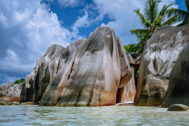 Anse-Quelle d 'Argent - enorme Granitflusssteine zwischen Kumpelbäumen auf tropischem sandigem Strand gegen blauen Himmel mit wei stockbilder